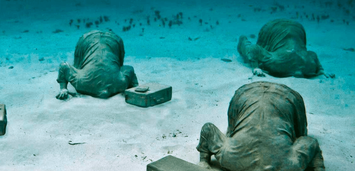 banquiers sculpture tete enfoncée dans le sable musée sous-marin de Cancun
