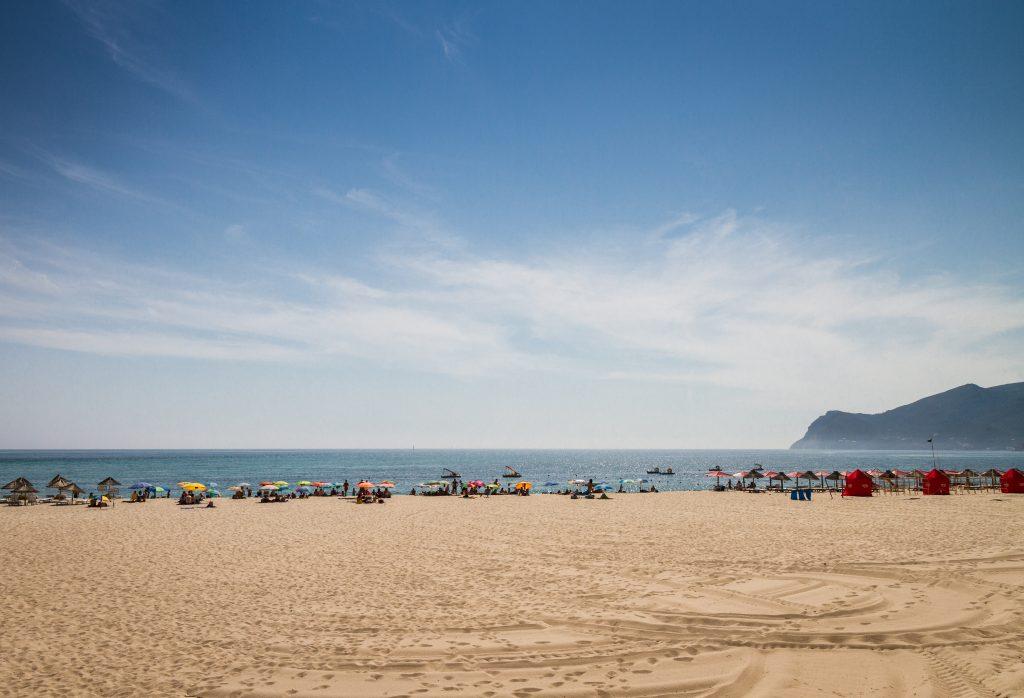 Praia de Figueirinha est appréciée pour son accessibilité et son cadre, magnifié par la montagne d'Arràbida qui se dessine en arrière-plan.